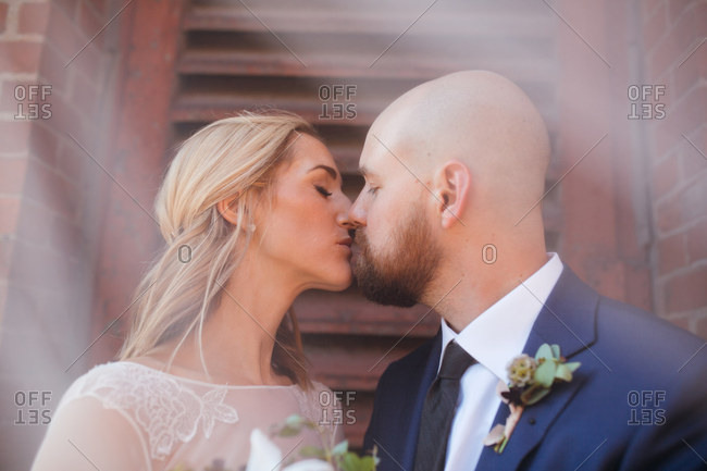 Bride and groom kissing with veil in front of lens