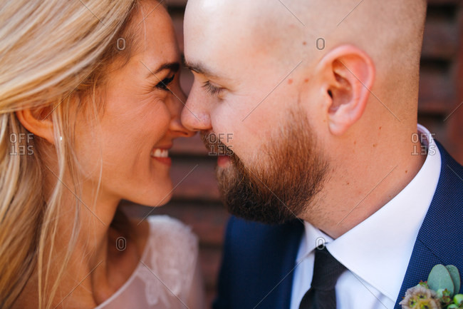 Playful braze nuzzling groom's nose on wedding day