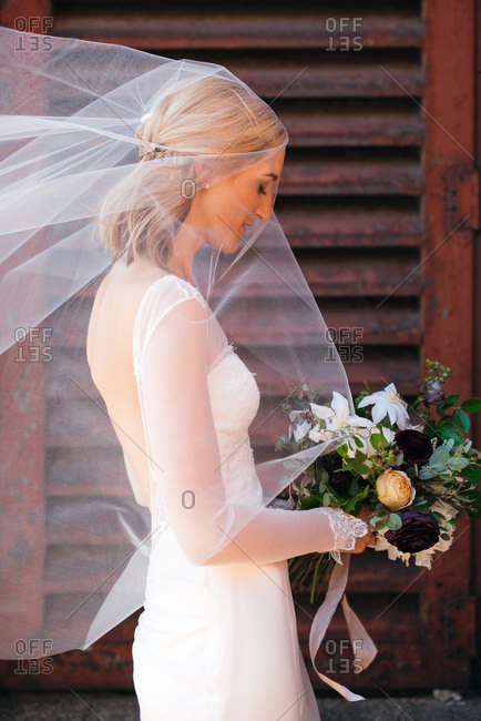 Bride closing eyes with veil blowing in wind