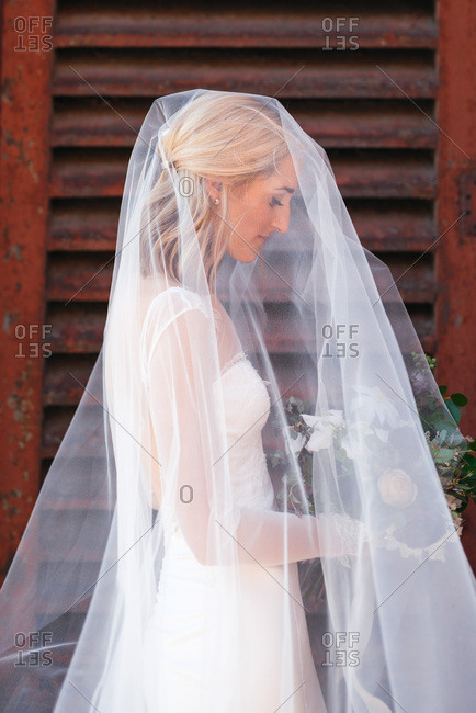 Profile view of bride waiting with bouquet and veil over head
