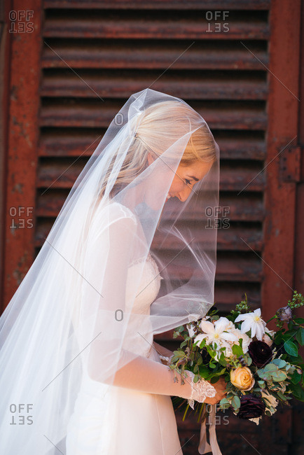 Bride grinning with head bowed and bouquet of flowers