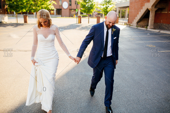 Couple walking alone together through wedding venue parking lot
