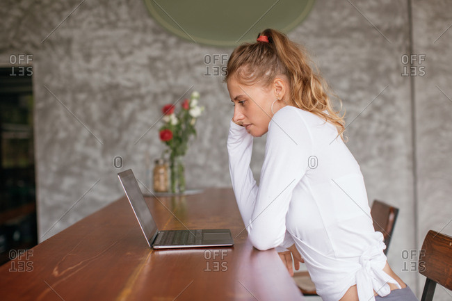 Young woman sitting at table looking at laptop computer