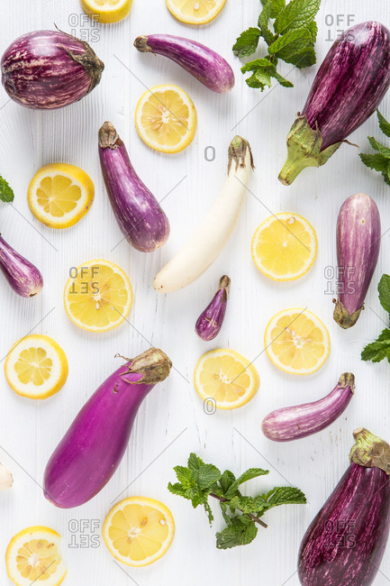 Eggplants and lemon slices on a white table