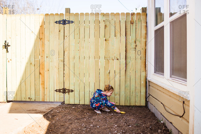 Little girl digging in dirt with little shovel