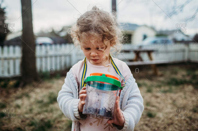 Little girl looking at her bug collection