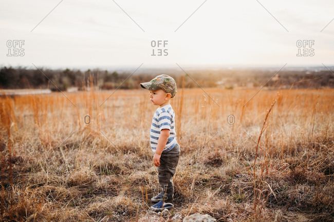 Toddler boy wearing camouflage hat in a field