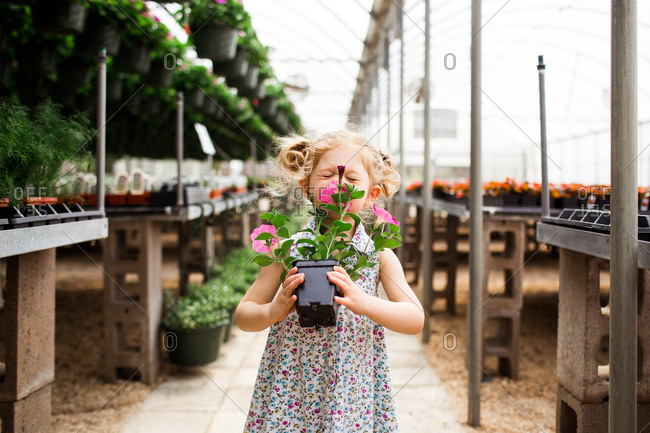 Little girl smelling flowers in a garden center