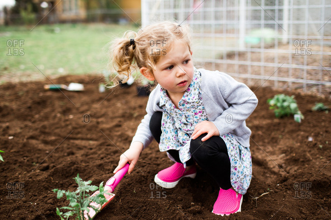 Close up of a little girl digging in garden with small shovel