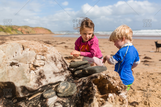 Children playing on driftwood at beach