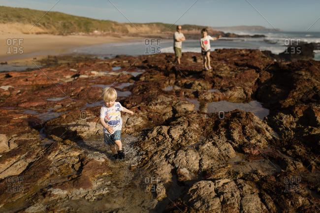 Family exploring rocky coastline