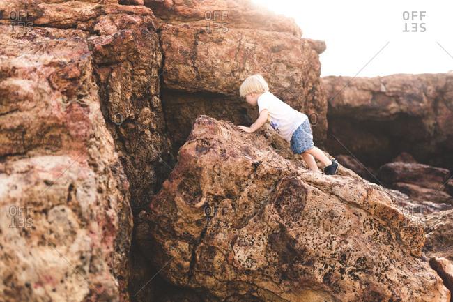 Boy exploring rocky coastline