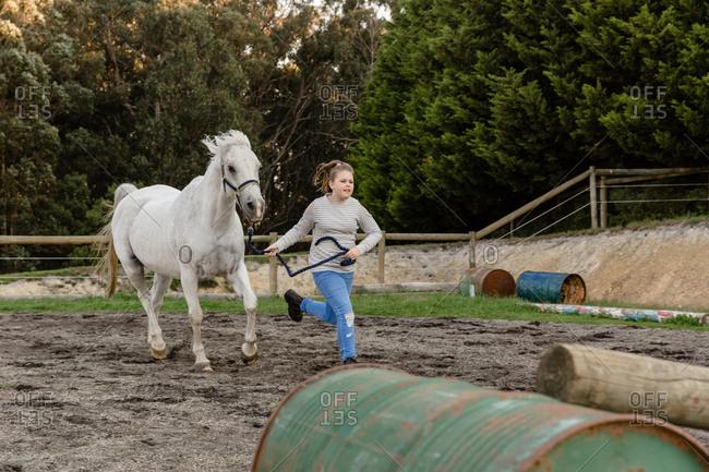 Girl running horse over jump