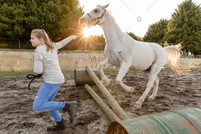 Girl running horse over jump