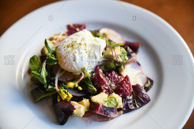 Freshly made salad topped with burrata cheese