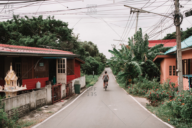 Bangkok, Thailand - March 16, 2018: Back view of unrecognizable man riding bicycle on asphalt road in suburbs.
