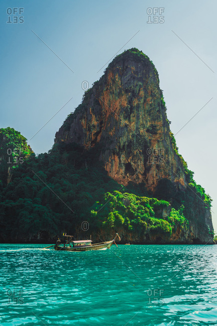 Bangkok, Thailand - February 4, 2018: Small boat sailing under coastal rock in blue ocean water.