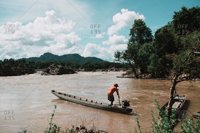 Rural Province, Laos - March 16, 2018: Unrecognizable man in casual clothes driving wooden canoe on dirty river in amazing countryside.