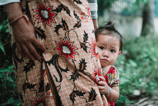 Rural Province, Laos - March 16, 2018: Adorable little child looking at camera while hiding behind crop mother in skirt.