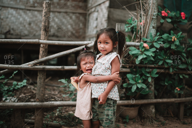Rural Province, Laos - March 16, 2018: Adorable Asian girl weeping and hugging sister while standing together on village street.