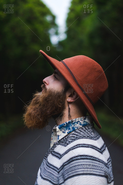 Side view of handsome bearded man in hat standing on asphalt road in green forest.