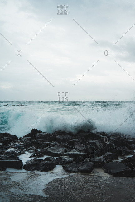 View to coastal rock and ocean wave in cloudy day.