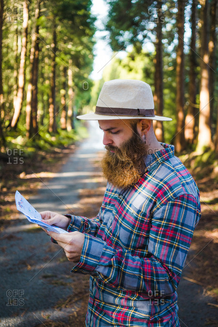 Bearded tourist standing with smartphone and map while navigating on road in forest.