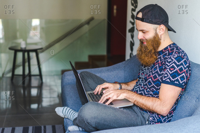 Cheerful bearded man sitting and typing on laptop on couch at home.