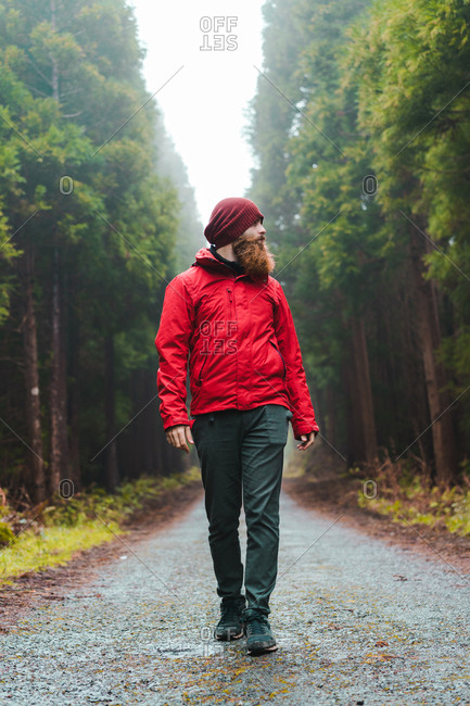 man in red jacket walking on road in forest with hands up.