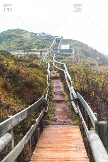 Perspective view to small path and wooden handrail leading to the hill in nature.