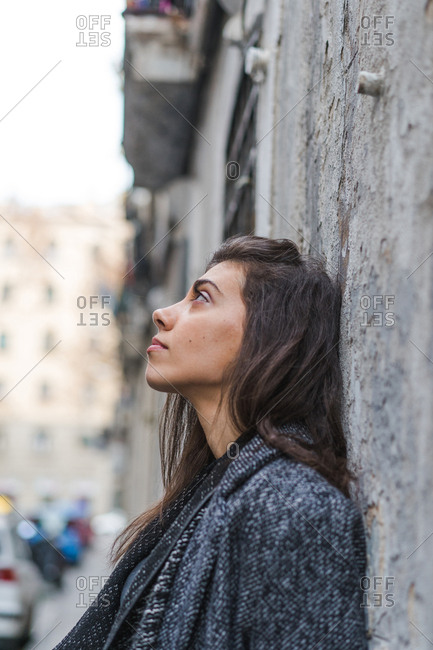 Young woman leaning on grungy door