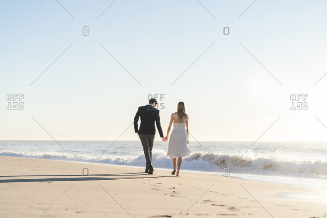 Romantic bride and groom strolling on beach