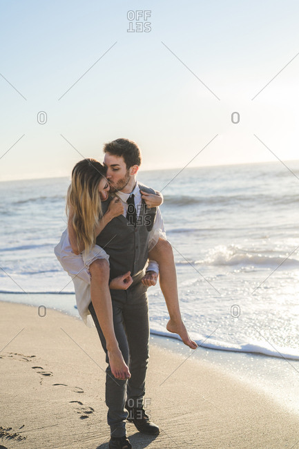 Groom carrying charming girl on back