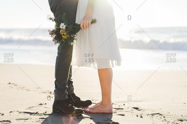 Crop bride with bouquet embracing groom