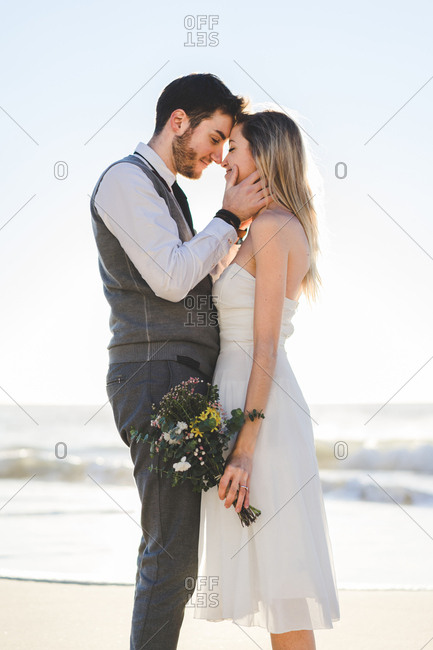 Bride with bouquet embracing groom