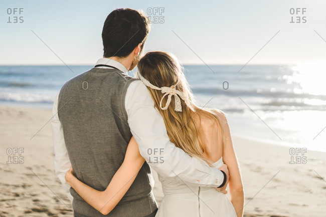 Bridal couple embraced on the beach