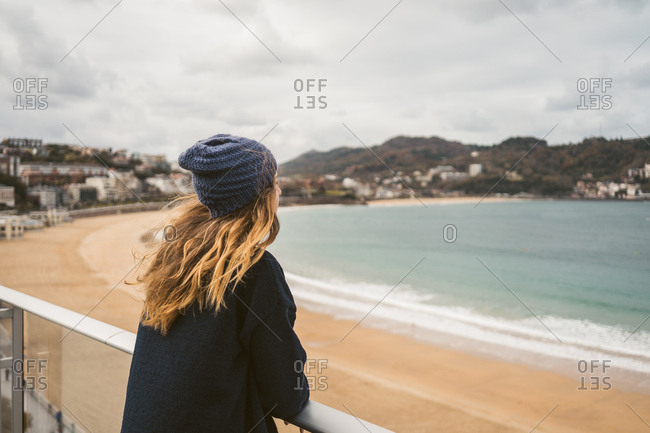 Side view of blonde woman leaning on handrail and looking away at sandy beach and ocean.