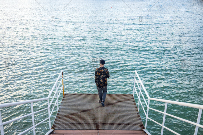 Adult man with cup of coffee standing on stairs at the ocean.