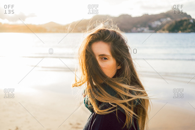 Young pretty dreamy woman standing on sandy beach and looking away in evening.