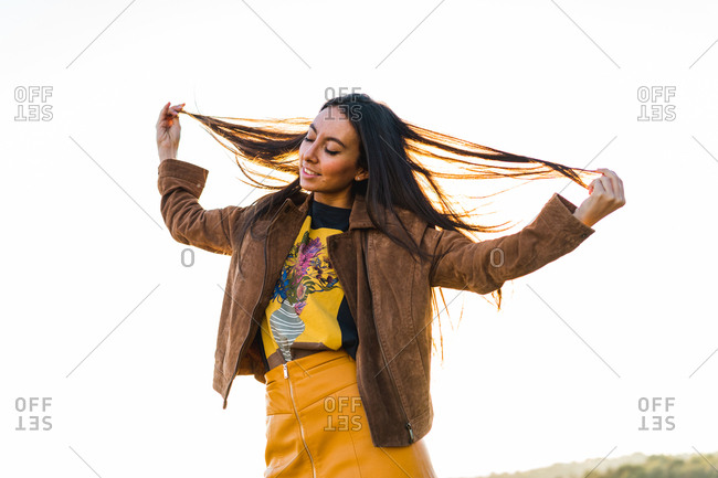 Cheerful woman playing with hair in nature