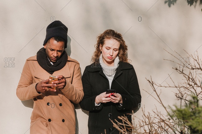 Couple in warm clothes with smartphones