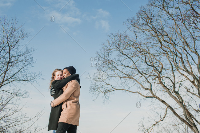 Cheerful multiethnic couple in warm clothes embracing at leafless trees in sunny day.