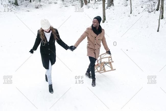 Happy multiethnic couple with sledge