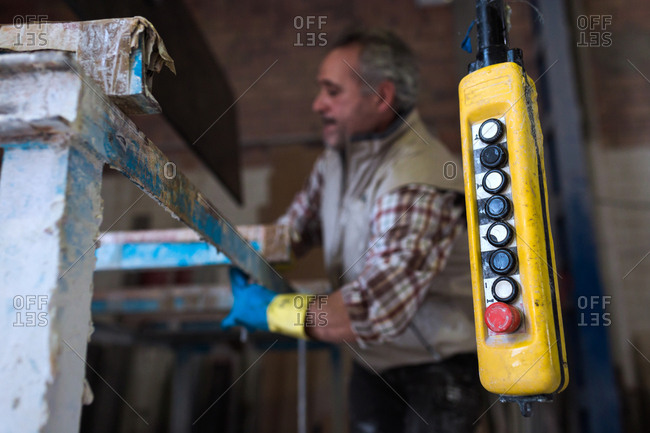 Yellow control panel and adult man standing at machine in workshop.