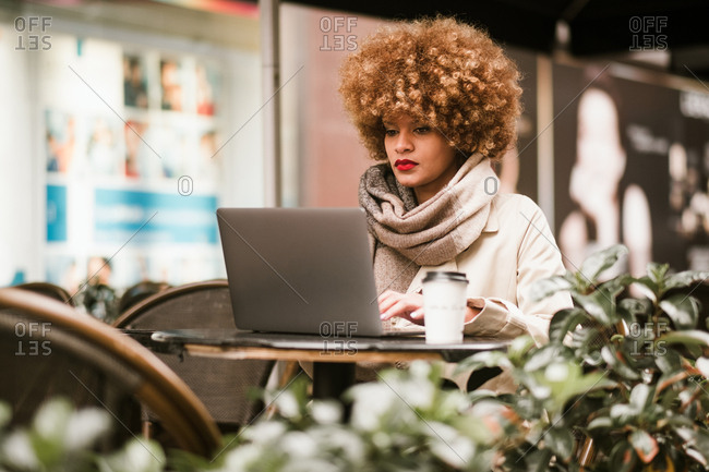 Pretty woman in stylish clothes sitting in cafe and browsing laptop.