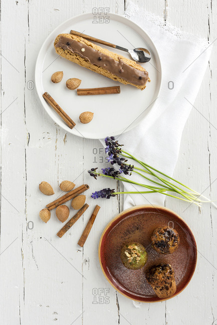 Bunch of beautiful flowers and cinnamon sticks lying near pastry and almonds on white timber background.