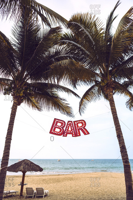 Red Bar sign between two palms on sandy beach at the ocean.