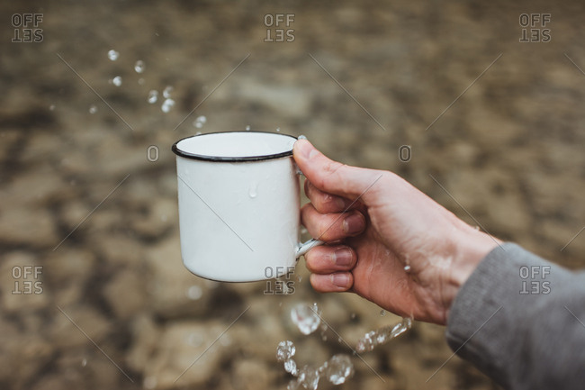 Hand splashing water from cup