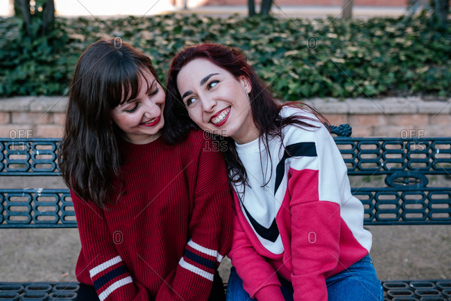 girlfriends sitting on the bench in a park