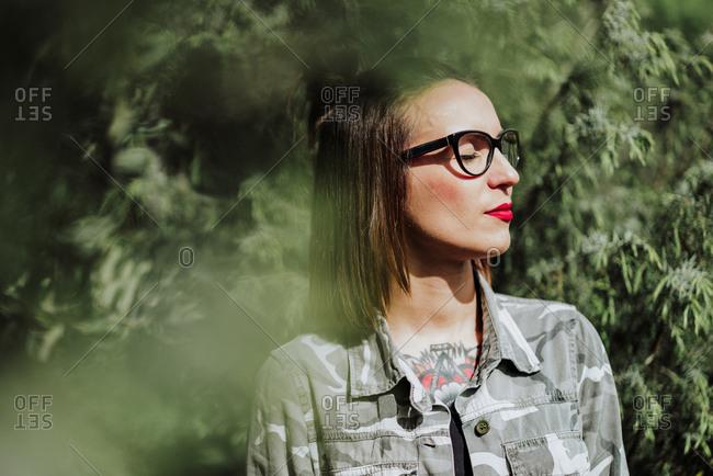 Stylish tattooed woman in nature